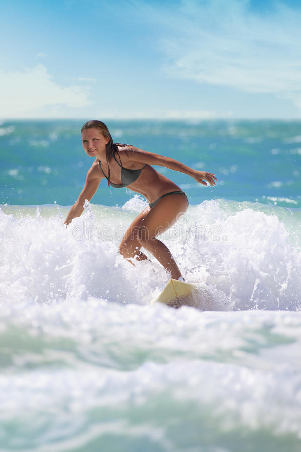 Young woman surfing. Young attractive woman on a surf board on the waves of the ocean