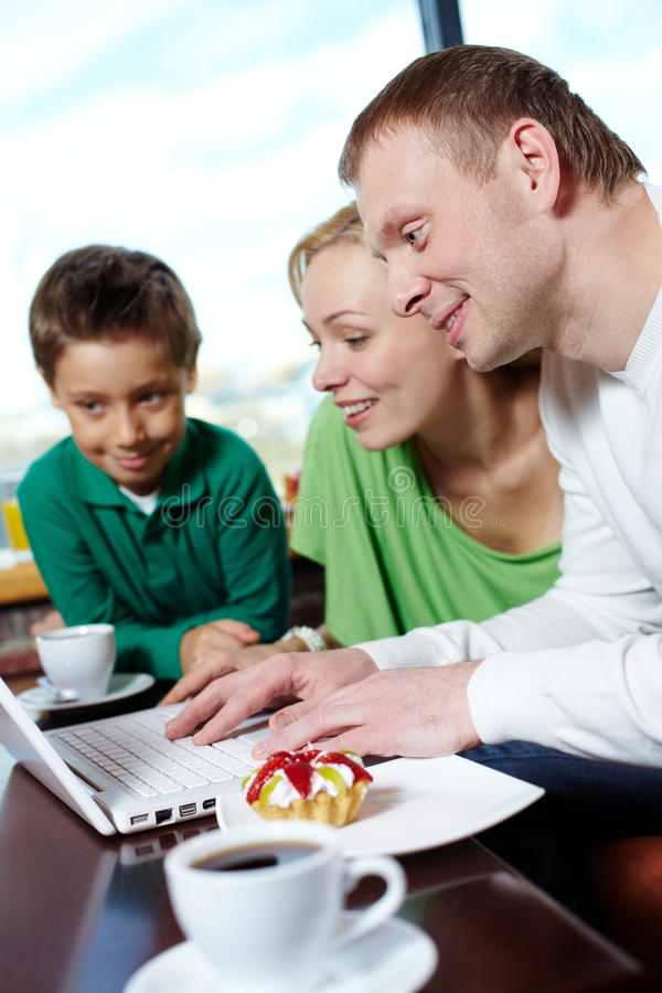 Surfing internet at cafe. Family of three spending time at a cafe surfing internet stock photography