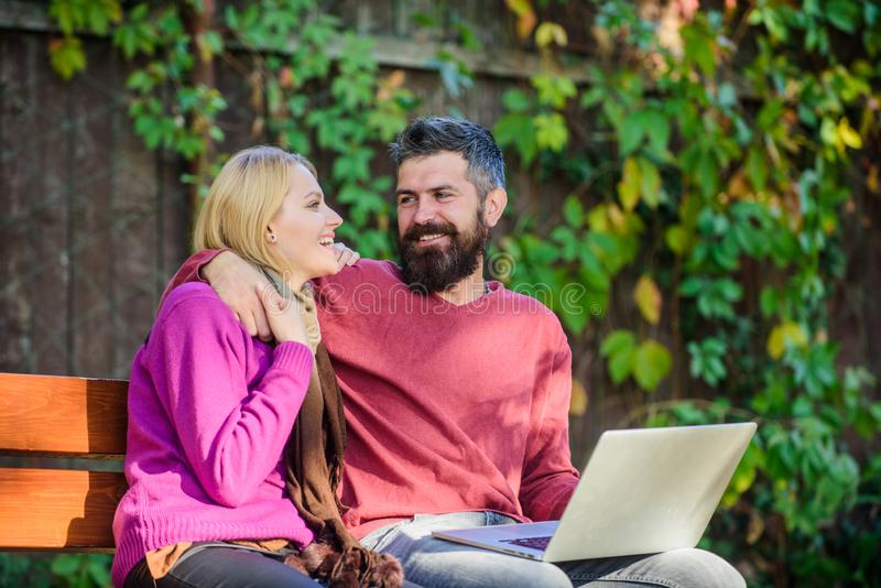 Surfing internet together. Couple with laptop sit bench in park nature background. Family surfing internet for. Interesting content. Internet surfing concept royalty free stock image