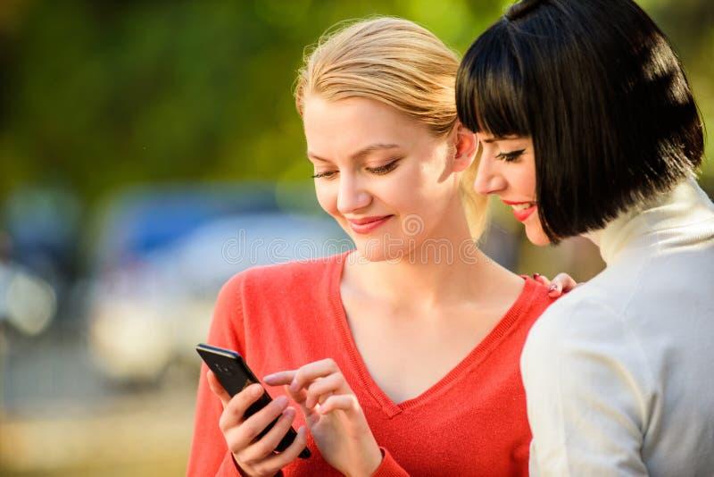 surfing internetu Komunikowa? online Dziewczyny komunikuje patrzejący telefon Zakup online Dwa kobiety z smartphone obraz royalty free