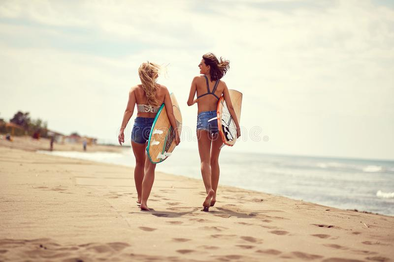 Surfing lifestyle. Surfer girls walking with board on the sandy beach. Surfing lifestyle. Surfer smiling girls walking with board on the sandy beach stock photo