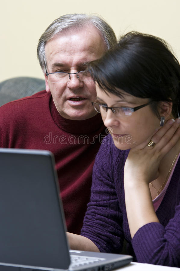 Surfing the net together. A woman (daughter) teaching a senior man (father) how to use a laptop. They both are looking focused on the screen
