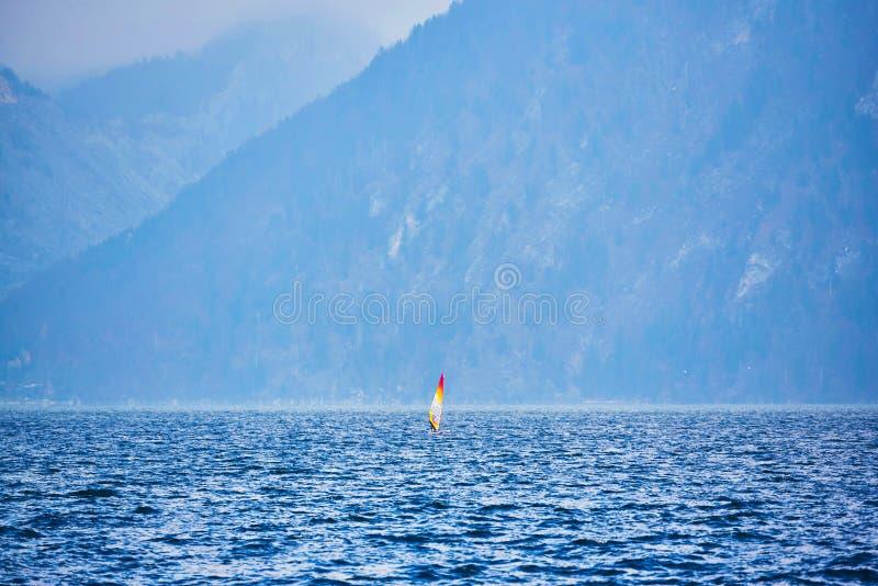 Surfing på sjölandskap och dimmiga berg på bakgrund Mansurfare på brädet med att segla att sväva på sjön royaltyfria foton