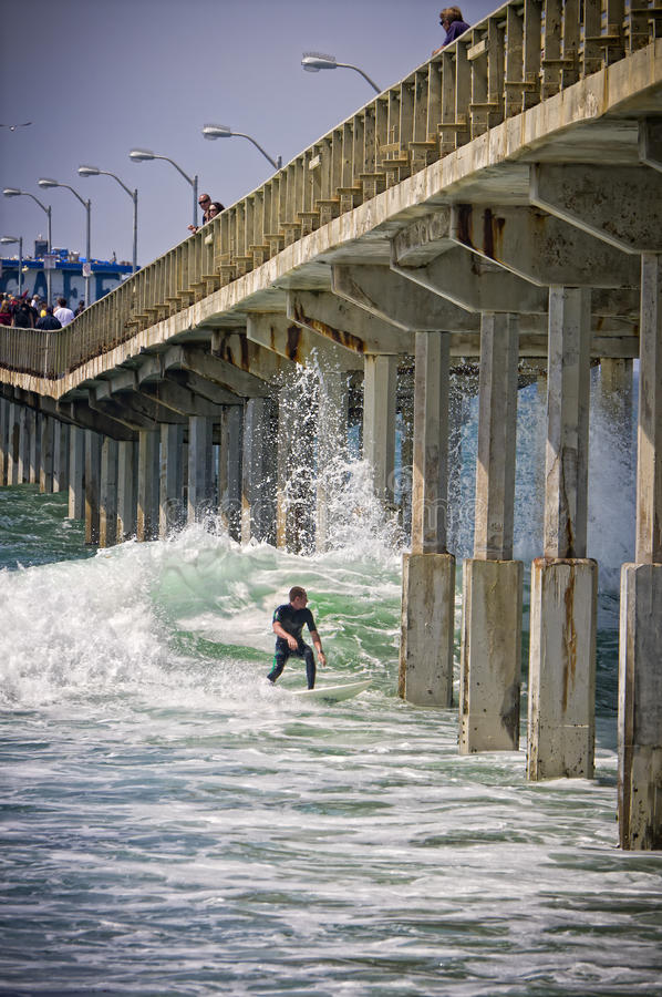 Surfing in San Diego, California. A male surfer in San Diego, California at the Ocean Beach Pier catches the big waves of the Pacific Ocean surf created by a stock photo