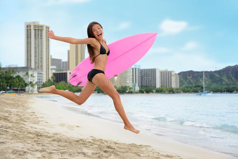 Surfing summer fun woman jumping of joy on beach with surfboard. Surf vacation lifestyle. Asian girl in bikini, sport and fitness. Surfing summer fun woman stock photography