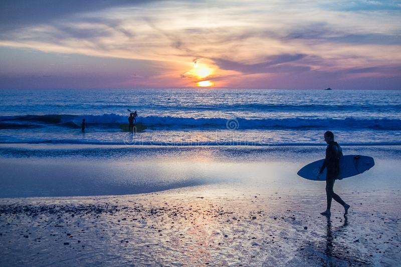 Surfing during sunset at San Clemente beach, California. Surfers still heading to the ocean royalty free stock photos