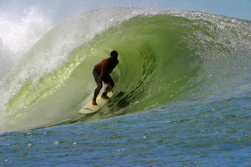 Surfing the Tube in Hawaii. A surfer riding deep in the tube of a wave while surfing in Hawaii royalty free stock images