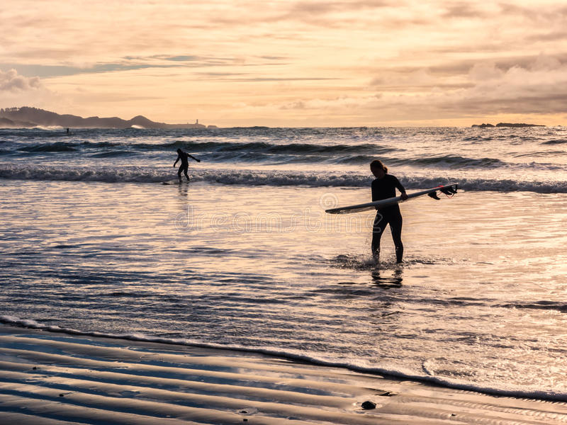 Surfing under a winter sunset. Surf boarders heading in from surfing under a winter sunset at Devil's Punch Bowl on the Oregon coast royalty free stock photo