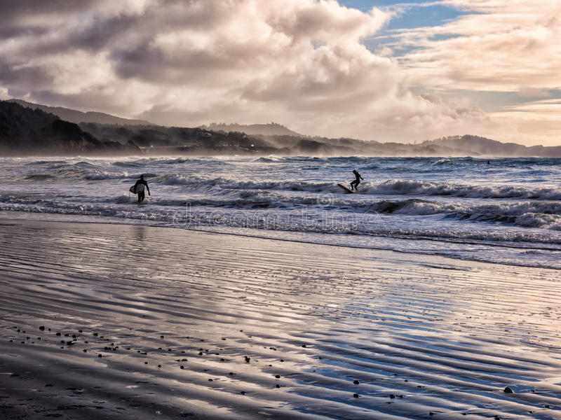 Surfing under a winter sunset. Surf boarders heading in from surfing under a winter sunset at Devil's Punch Bowl on the Oregon coast stock image