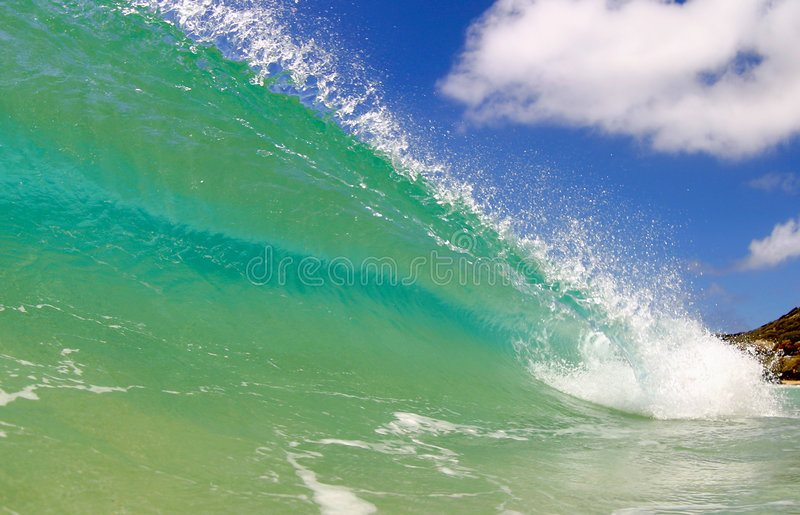 Surfing Wave in the Pacific Ocean on a Sunny Day. Photo of a clean and clear surf wave at Sandy Beach on the island of Oahu, Hawaii stock photography