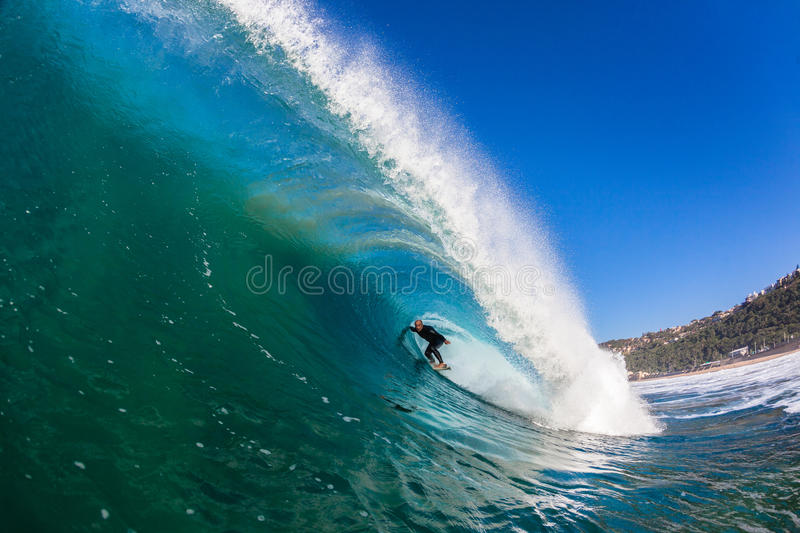 Surfer Big Wave Tube Ride. Surfing action rider inside a big hollow wave.Swimming water photo image of the Surfer stock images