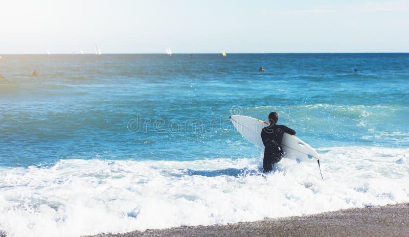 Surfingbräda för surfareflickainnehav på bakgrundshavsscape, sandstrandkustlinje Hav för sikt för panoramahorisontperspektiv, sol royaltyfria bilder
