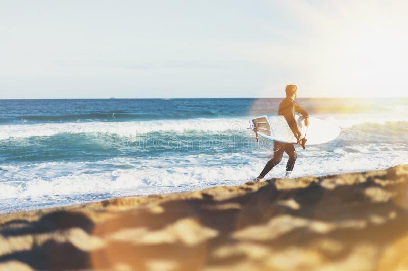 Surfingbräda för surfaremaninnehav på bakgrundshavsscape, sandstrandkustlinje Hav för sikt för panoramahorisontperspektiv, sollju royaltyfri fotografi