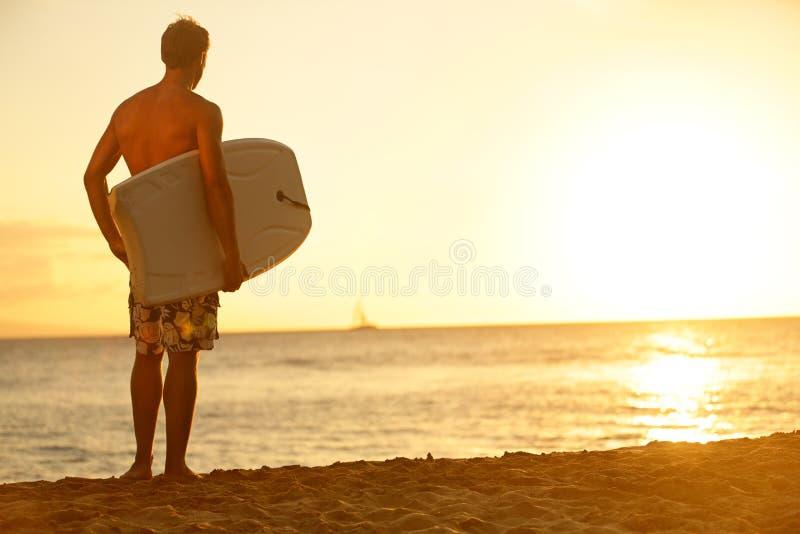 Surfingowa mężczyzna na plaży przy zmierzchu mienia bodyboard zdjęcia stock