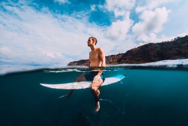 Surfingowa mężczyzna relaksuje przy * w oceanie z surfboard zdjęcia stock