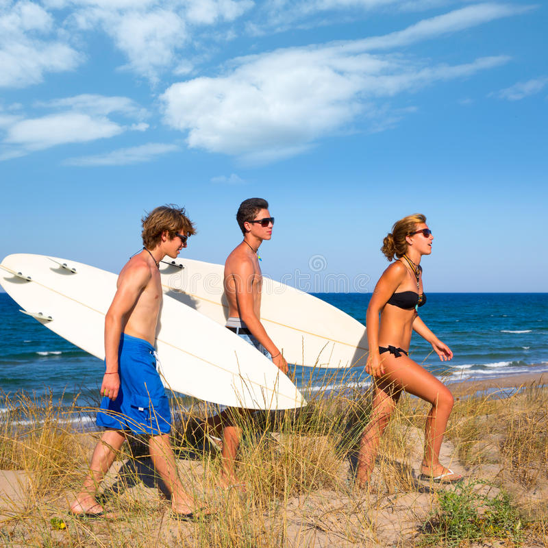 Surfingowa nastoletni grupowy odprowadzenie na wydmowym sposobie wyrzucać na brzeg obrazy stock