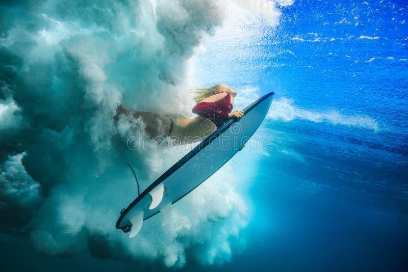 Surfingowiec dziewczyna pod ocean falą zdjęcie stock