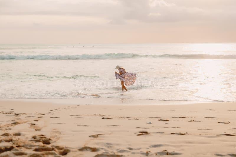 Surfingowiec dziewczyna z surfboard na plaży przy zmierzchem obrazy stock