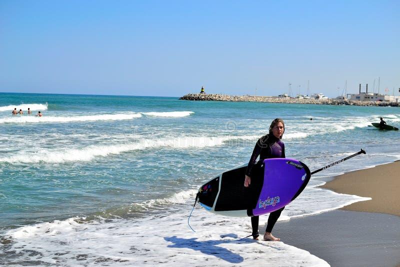 surfingowiec dziewczyna z surfboard na Torremolinos plaży, Costa Del Zol, Hiszpania zdjęcie stock