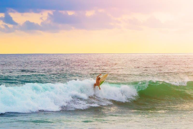 Surfingowiec jedzie fala na surfboard fotografia stock
