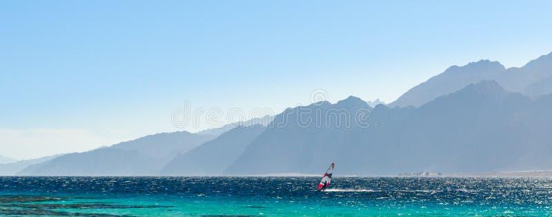 Surfingowiec jedzie w Czerwonym morzu przeciw tłu wysokie skaliste góry i niebieskie niebo z chmurami w Egipt Dahab zdjęcie royalty free