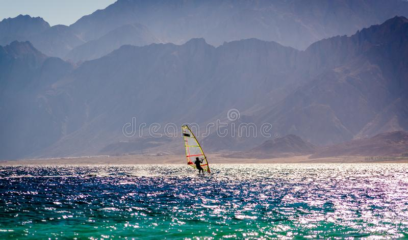 Surfingowiec przejażdżka w morzu na tle skalisty wybrzeże w Egipt Dahab obrazy royalty free