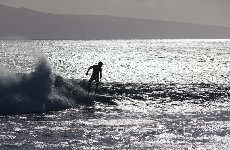 Surfingowiec silhoutted przeciw srebnym fala fotografia stock