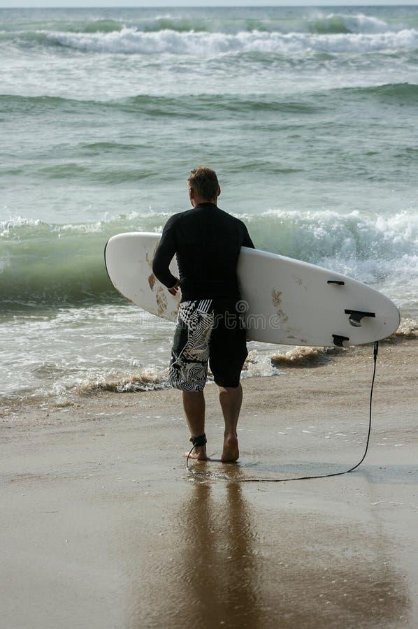 Surfingowiec z surfboard na plażowym dopatrywaniu przy oceanem zdjęcie royalty free