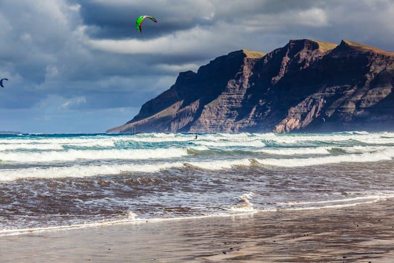 Surfingowowie i kiters w wodzie na Famara wyrzucać na brzeg zdjęcie stock