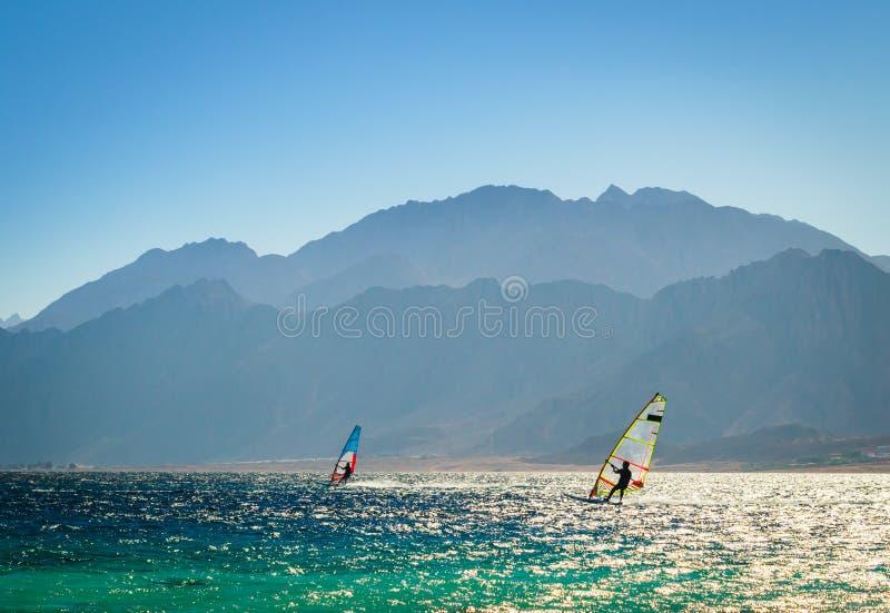 Surfingowowie jadą w morzu na tle skalisty wybrzeże w Egipt Dahab zdjęcie royalty free