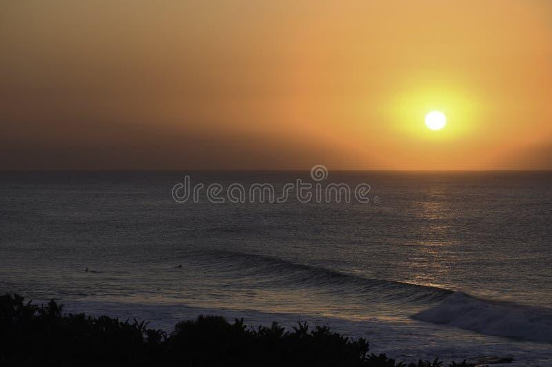 Surfingowowie Ogląda The Sun Nad horyzontem, Uvongo, Południowa Afryka zdjęcia royalty free