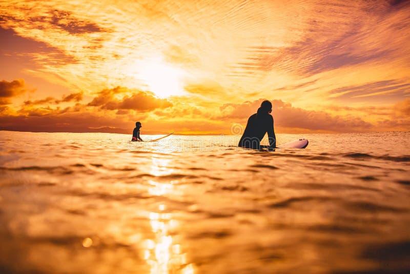 Surfingowowie w oceanie przy zmierzchem lub wschodem słońca Para surfingowiec i ocean obrazy stock