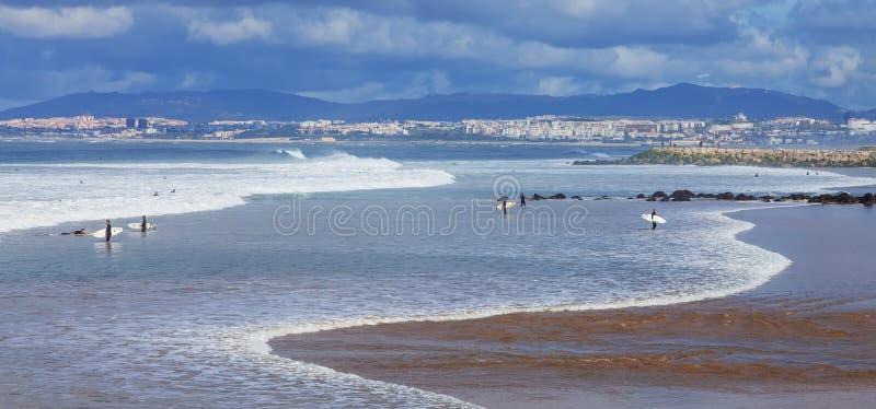 Surfingowowie w plaży z Lisbon w tle zdjęcia stock