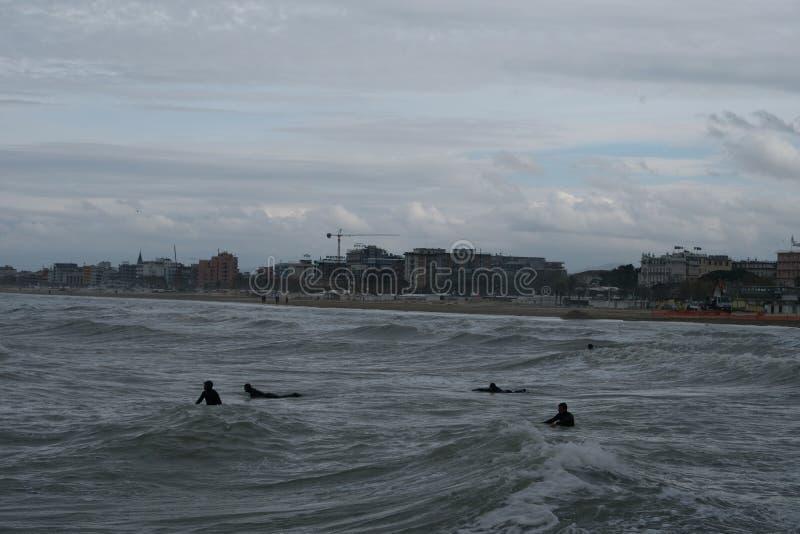 Surfingowowie w zimie w Rimini, Włochy Opróżnia podczas przyprawiającego daleko obraz stock