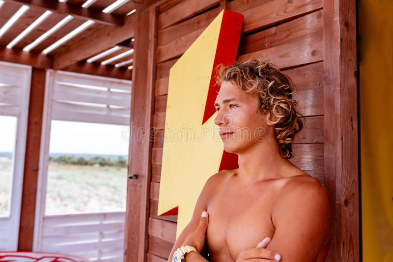 Surfista attceractive novo do indivíduo que está no terraço de uma escola da ressaca que olha para fora na distância imagens de stock