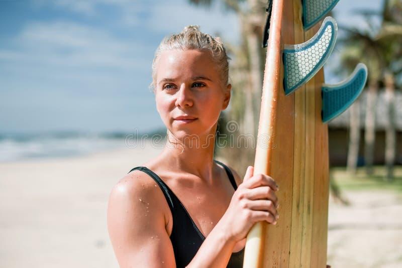 Surfista bonito da menina do atleta com uma placa no nascer do sol Estilo de vida saudável e resto ativo imagens de stock royalty free