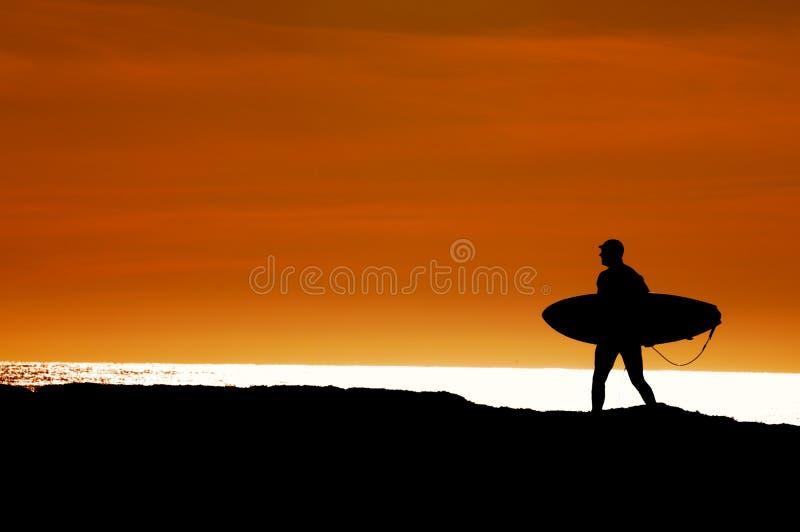 Surfista che cammina all'oceano fotografia stock