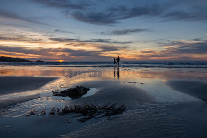 Surfista che cammina dal mare sotto un cielo drammatico di tramonto fotografie stock libere da diritti
