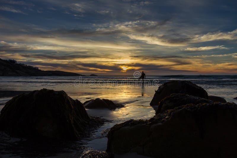 Surfista che cammina dal mare sotto un cielo drammatico di tramonto fotografia stock