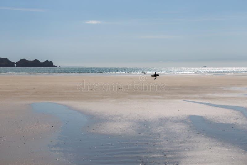 Surfista che cammina sopra l'ampia spiaggia sabbiosa di estate con il mare e la c rocciosa immagini stock