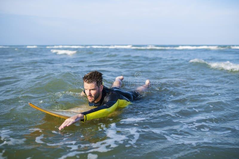 Surfista che rema attraverso l'acqua fotografia stock