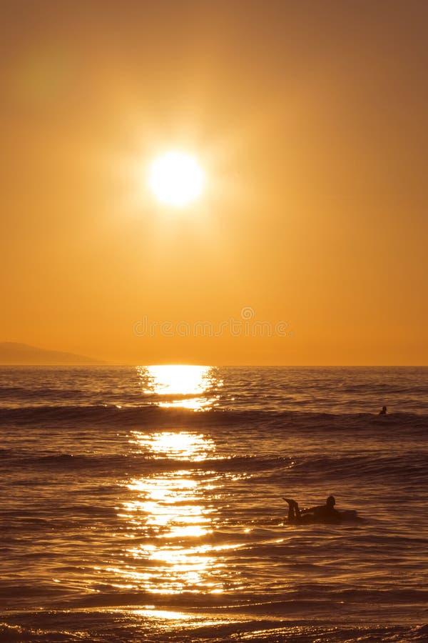 Surfista che rema nel mare al tramonto fotografie stock