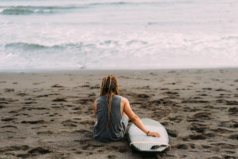 Surfista com os dreadlocks com o surfingboard perto do oceano imagens de stock