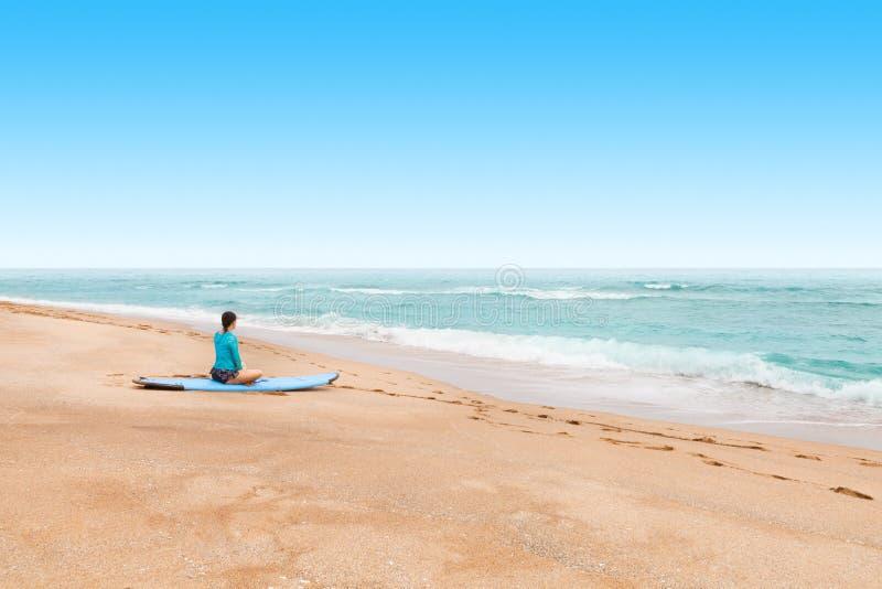 Surfista da jovem senhora que espera em um litoral pelo as ondas grandes a vir fotografia de stock