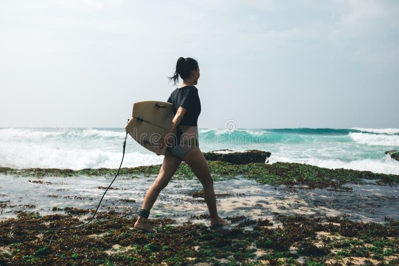 Surfista da mulher que anda com prancha imagem de stock