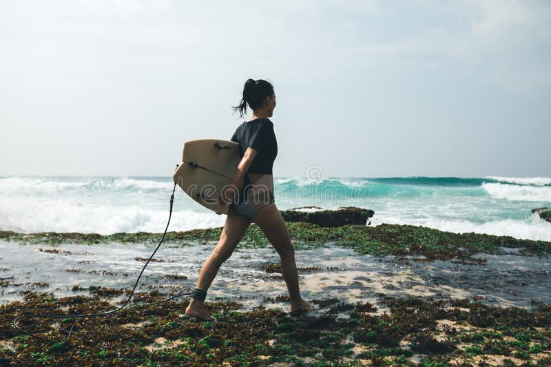 Surfista della donna che cammina con il surf immagine stock
