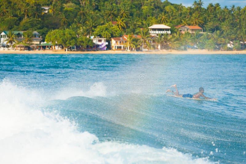 Surfista dello Sri Lanka che rema sopra l'onda Unawatuna fotografia stock