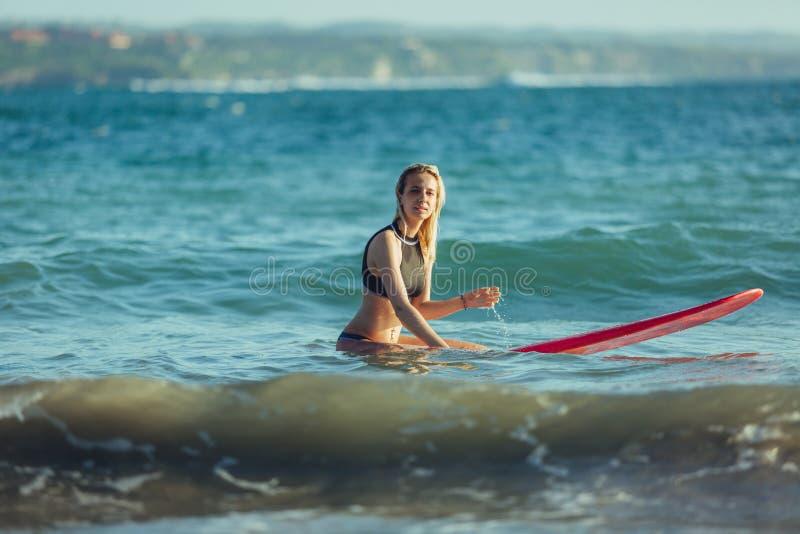 surfista fêmea atrativo que senta-se na prancha imagens de stock