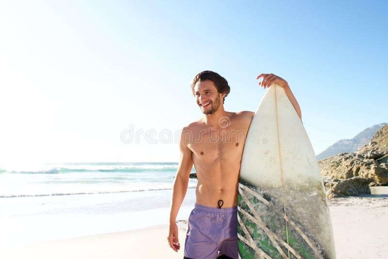 Surfista masculino feliz que está com sua placa na praia fotografia de stock royalty free