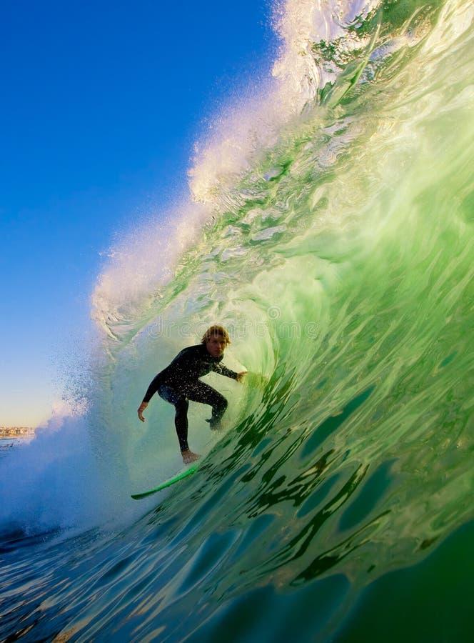 Surfista na câmara de ar que monta uma onda grande
